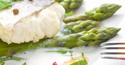 Fish fillet with asparagus foam sauce and fork, makro, soft focus